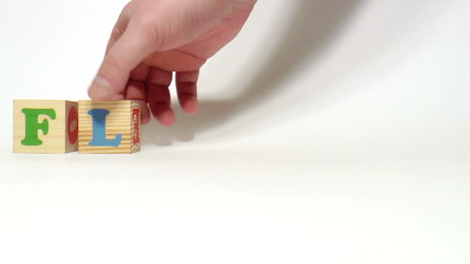 The video shows Flowers word built of wooden blocks