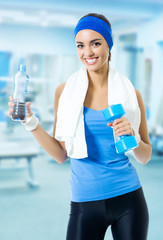Woman in sport wear with water, at gym