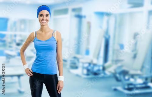 Happy young woman at gym, with copyspace