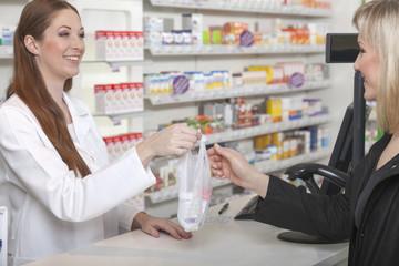 Apotherkin überreicht Tüte mit Medikamenten
