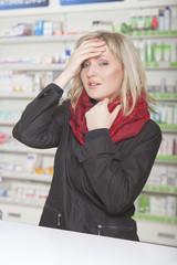Kundin mit Kopfschmerzen in der Apotheke