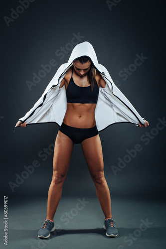 Attractive athletic young woman posing in studio on dark backgro - 80599017