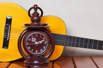 old clock with classical guitar in an empty room.