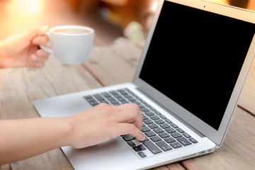 Closeup of business woman hand typing on laptop keyboard and cof