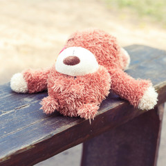Lonely abandoned on the wooden bench lonely teddy bear toy