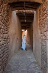 Saudian walking inside the walls of Al-Ula Old City, Saudi Arabi
