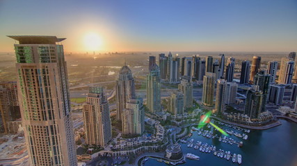 Sunrise in Dubai Marina with towers and harbor with yacht from