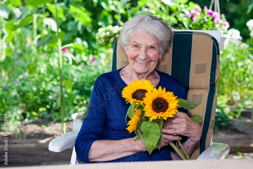 Leinwanddruck Bild Happy Old Lady Sitting on Chair Holding Sunflowers.