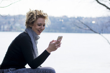 happy young curly blond woman sitting by the river and typing on