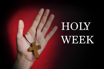 man hand with a wooden cross and the text holy week