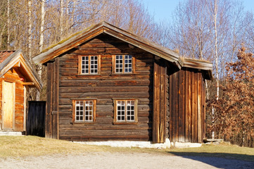 Norwegian building of round logs with small shutters