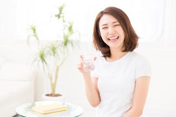 部屋で水を飲む女性