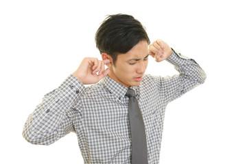 耳を塞ぐビジネスマン