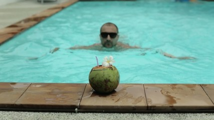 A man swims in the pool and drinking coconut
