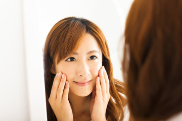 Smiling young woman looking mirror in  bedroom