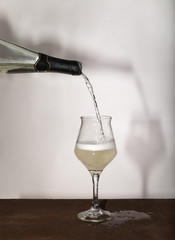 White wine bottle pouring wineglass on white background
