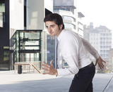 Determined businessman running and urban background poster