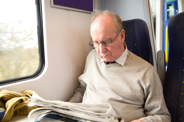 old man reading the newspaper on the train