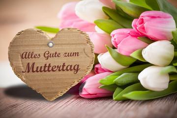 Blumen und herzförmige Nachricht zum Muttertag