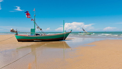Clean beach and fishing boat on daylight
