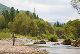 Fly fisherman fishing in mountain river