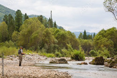 Foto op Canvas Vissen Fly fisherman fishing in mountain river
