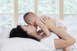 Happy mother kissing baby on bed