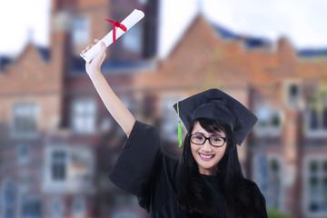 Happy student in graduation gown outdoor