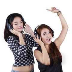 Happy teenage girls listening music