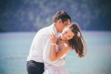 groom embrace bride standing on sand beach