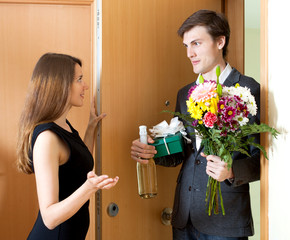 Smiling man giving gifts to beautifull woman at home door