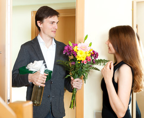 Young man giving gifts to cute woman at home