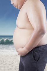 Sad man looking at his fat tummy