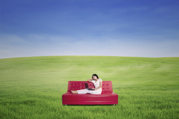 Woman using laptop on sofa at meadow