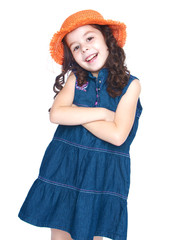 Smiling girl in a denim dress and orange hat