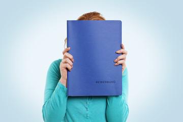 Frau versteckt sich hinter Bewerbungsmappe