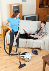 woman doing house cleaning during man resting