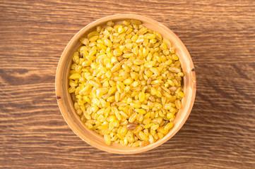 Cereal bulgur in a wooden bowl closeup