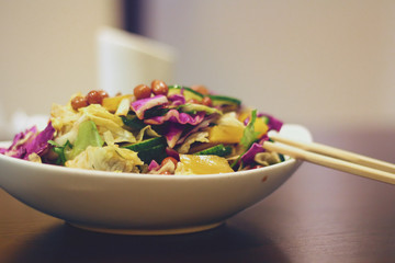 Delicious vegetable salad on wood table with chopsticks