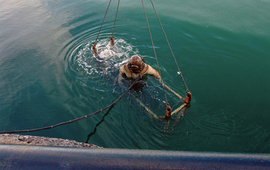 Diver in heavy spacesuit plunges into the sea.