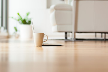 A laptop and cup of tea on the floor in the living room