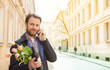 Man with wine and flower bouquet talking on a mobile phone