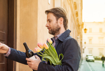 Man with wine and flower bouquet ringing doorbell