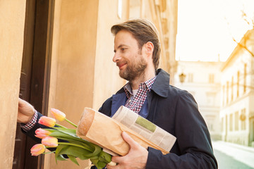 Man with baguette, newspaper and flower bouquet ringing doorbell