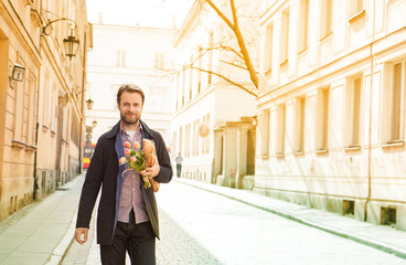 Happy man with flower bouquet walking down the street