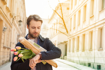 Man with baguette, and flower bouquet looking at watch