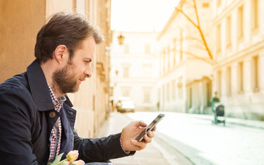 Forty years old man looking at a mobile phone - city