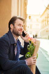 Man with flower bouquet talking on a mobile phone - city