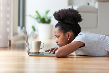African American woman using a laptop in her living room - Black