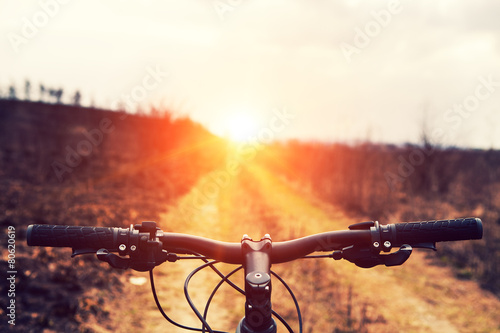 canvas print picture Mountain biking down hill descending fast on bicycle. View from